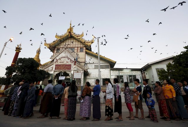 People line up outside a Buddhist prayer hall to vote during the general election in Mandalay, Myanmar, November 8, 2015. Voting began on Sunday in Myanmar's first free nationwide election in 25 years, the Southeast Asian nation's biggest stride yet in a journey to democracy from dictatorship. (Photo by Olivia Harris/Reuters)