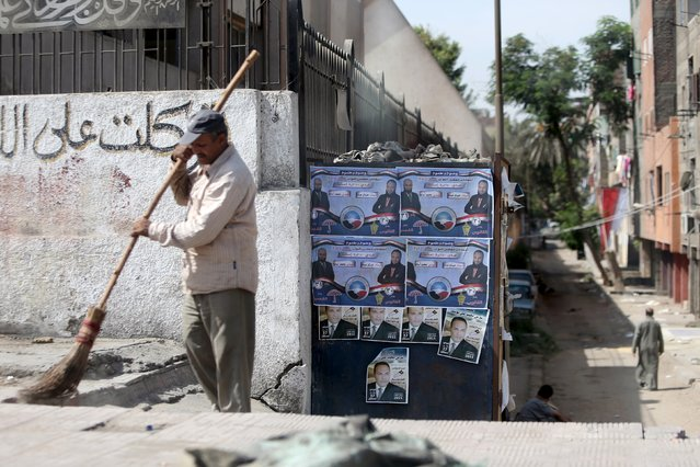 A cleaner sweeps the ground near election posters for parliamentary candidates of Nour party Hossam Abdo and Mohammed Osama in the Imbaba district of Giza, Egypt, October 13, 2015. (Photo by Mohamed Abd El Ghany/Reuters)