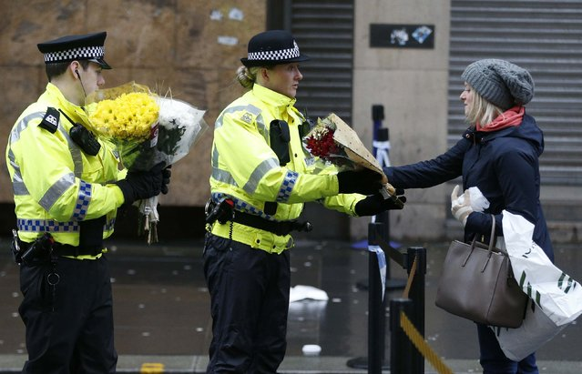 A woman gives flowers to a police officer near the scene where a refuse truck crashed into pedestrians in George Square, Glasgow, Scotland December 23, 2014. Six people were killed when a rubbish lorry ran out of control and careered down a pavement crowded with Christmas shoppers in Glasgow, Scotland, on Monday, police said. (Photo by Russell Cheyne/Reuters)