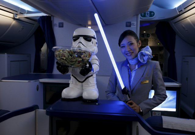 A stewardess holding a lightsabre poses for photos with visitors during a tour of the Star Wars themed All Nippon Airways ANA R2D2 Boeing 787 Dreamliner aircraft at Singapore's Changi Airport November 12, 2015. (Photo by Edgar Su/Reuters)