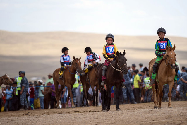 This picture taken on July 11, 2015 shows 13-year-old jockey Purevsurengiin Togtokhsuren (front L) arriving at the starting line to compete in the 'Inkhnas' (over five-year-old horses) horse race in Khui Doloon Khudag, some 50 kms west of Ulan Bator. (Photo by Johannes Eisele/AFP Photo)