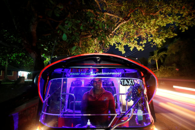 A three wheel driver waits for a customer inside his vehicle on the side of a main road in Kesbewa, Sri Lanka, October 18, 2016. (Photo by Dinuka Liyanawatte/Reuters)