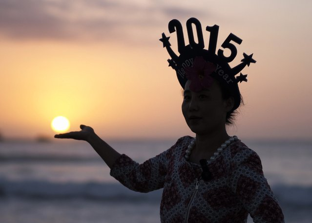 A tourist poses for a friend (not pictured) as if to hold the sun as New Year's revellers welcome the first sunrise of 2015 on Sydney's Bondi beach, January 1, 2015. (Photo by Jason Reed/Reuters)