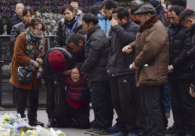 A woman, third from left, grieves as she is comforted by other relatives of a New Year's Eve stampede victim at the site of the tragic accident in Shanghai, China, Tuesday, January 6, 2015. (Photo by AP Photo)