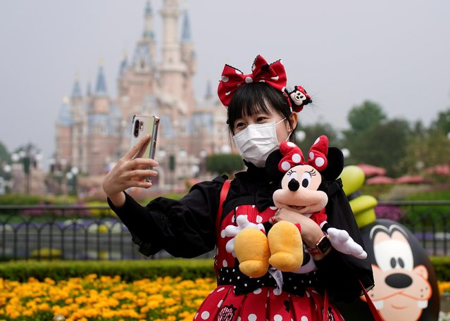 A visitor dressed as a Disney character takes a selfie while wearing a protective face mask at Shanghai Disney Resort as the Shanghai Disneyland theme park reopens following a shutdown due to the coronavirus disease (COVID-19) outbreak, in Shanghai, China on May 11, 2020. (Photo by Aly Song/Reuters)