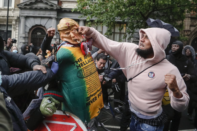 A demonstrator punches a puppet depicting US President Donald Trump during a Black Lives Matter march in London, Saturday, June 6, 2020, as people protest against the killing of George Floyd by police officers in Minneapolis, USA. Floyd, a black man, died after he was restrained by Minneapolis police while in custody on May 25 in Minnesota. (Photo by Frank Augstein/AP Photo)