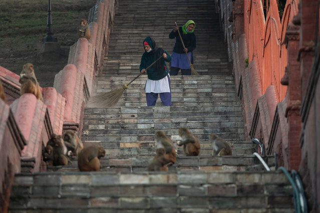 Workers clean the premises of Pashupatinath temple in Kathmandu, Nepal, December 16, 2020. The Pashupatinath Temple in Nepal reopened for devotees on Wednesday morning, almost eight months after it was shut due to the COVID-19 pandemic. (Photo by Xinhua News Agency/Rex Features/Shutterstock)