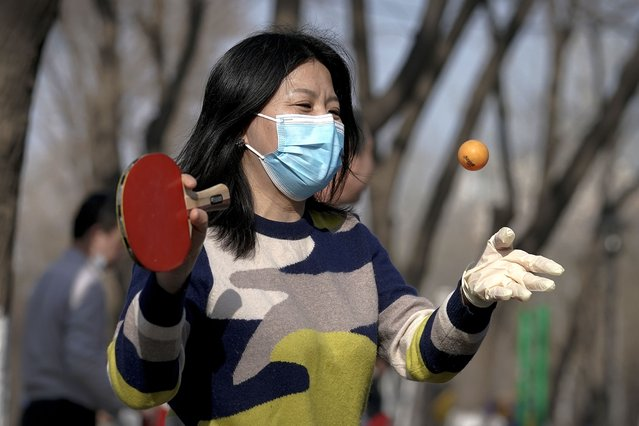 A woman wearing a face mask and a disposable glove to help curb the spread of the coronavirus plays table tennis at a public park during the lunch break in Beijing, Tuesday, January 26, 2021. Countries must cooperate more closely in fighting the challenges of the pandemic and climate change and in supporting a sustainable global economic recovery, Chinese President Xi Jinping said on Monday in an address to the World Economic Forum. (Photo by Andy Wong/AP Photo)