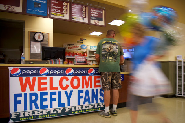 """A grocery store customer departs with a balloon bouquet past a sign stating """"WELCOME FIREFLY FANS"""" on the second day of the Firefly Music Festival in Dover, Delaware June 15, 2018. (Photo by Mark Makela/Reuters)"""