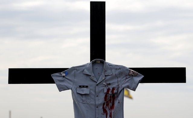 A police officer uniform placed by the NGO Rio de Paz (Peace Rio) is pictured on a cross on Copacabana beach, in memory of police officers killed in Rio de Janeiro, Brazil, December 10, 2015. Rio de Paz placed 61 pictures of police officers killed in confrontations with criminals in 2015 in Rio de Janeiro, according to the NGO. (Photo by Sergio Moraes/Reuters)