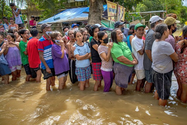 Residents affected by Typhoon Vamco queue in floodwaters to receive relief goods on November 16, 2020 in Tuguegarao, Cagayan province, Philippines. The Cagayan Valley region in northern Philippines saw its worst flooding in 48 years after a dam released massive amounts of rainwater brought about by Typhoon Vamco. The country continues to reel from the widespread destruction caused by this year's deadliest cyclone which has killed at least 67 people. (Photo by Ezra Acayan/Getty Images)