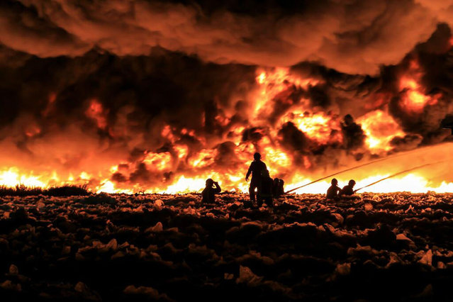 Fire fighters tackle a large blaze at a recycling centre in Smethwick, near Birmingham, central England July 1, 2013 in a handout picture provided by the West Midlands Fire Service. The fire service said they suspected the blaze was started when a Chinese lantern, a collapsible paper lantern lit by a candle, drifted into the centre which holds 100,000 tonnes of recycled paper and plastic. Up to 200 firefighters and 40 fire engines have been deployed. (Photo by Reuters/West Midlands Fire Service)