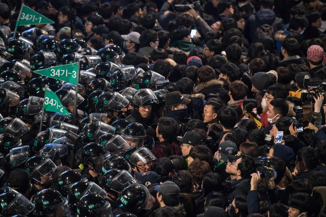 Protesters stand before police during an anti-government protest in the Gwanghwamun area of central Seoul on November 12, 2016. (Photo by Ed Jones/AFP Photo)