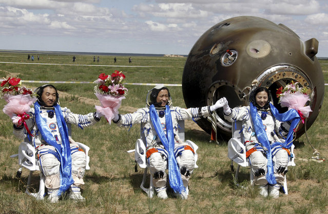 Chinese astronauts, from left, Zhang Xiaoguang, Nie Haisheng and Wang Yaping celebrate after stepping out of the re-entry capsule of China's Shenzhou 10 spacecraft following its successful landing at the main landing site in Siziwang Banner, north China's Inner Mongolia Autonomous Region, on June 26, 2013. (Photo by AP Photo via The Atlantic)