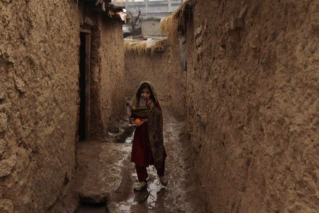 A girl walks on a muddy alley on her way home in a slum area on the outskirts of Islamabad January 21, 2015. (Photo by Faisal Mahmood/Reuters)