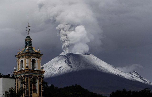 A plume of ash and steam rise from the Popocatepetl volcano overshadowing the Catholic church in Santiago Xalizintla, Mexico, on July 7, 2013. Just east of Mexico City, the volcano has spit out a cloud of ash and vapor 2 miles high over several days of eruptions. Mexico's National Center for Disaster Prevention raised the volcano alert from Stage 2 Yellow to Stage 3 Yellow, the final step before a Red alert, when possible evacuations could be ordered. (Photo by Marco Ugarte/Associated Press)