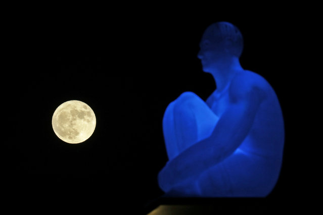 The supermoon rises behind one of the seven statues by spanish artist Jaume Plensa on Massena square in Nice, France, November 14, 2016. (Photo by Eric Gaillard/Reuters)