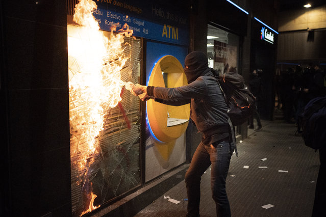 A protestor try to burn a bank branch after breaking the window following a protest condemning the arrest of rap singer Pablo Hasél in Barcelona, Spain, Saturday, February 27, 2021. (Photo by Emilio Morenatti/AP Photo)