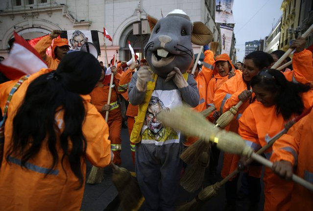Street sweepers clean a man dressed as a rat representing corruption, during a protest at San Martin plaza, in Lima, Peru, Thursday, July 19, 2018. The latest scandal to embroil this South American nation has ensnared some of the country's highest-ranking judges and political officials and comes just four months after then-President Pedro Pablo Kuczynski stepped down in a separate corruption probe. (Photo by Martin Mejia/AP Photo)