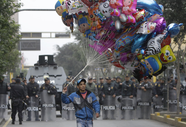 A balloon vendor walks in front of a group of riot police standing guard during an anti-government demonstration that was taking place as Peru's President Ollanta Humala delivered his State of the Nation address, in Lima, Peru, Sunday, July 28, 2013. Demonstrators claim Humala has not delivered on his promises to reduce crime and they say the political system does not represent them. (Photo by Martin Mejia/AP Photo)