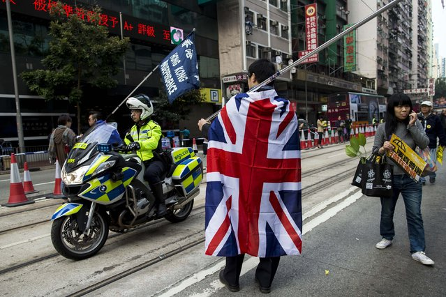 A police on a motorcycle rides past a pro-democracy protester draped with a British national flag during a march in the streets to demand universal suffrage in Hong Kong February 1, 2015. Several thousand pro-democracy protesters returned to the streets of Hong Kong on Sunday in the first large-scale rally since protests rocked the global financial hub late last year. (Photo by Tyrone Siu/Reuters)