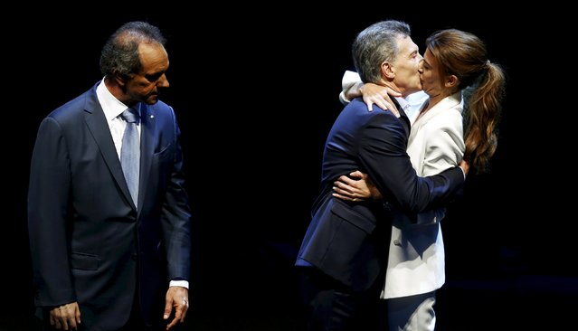 Mauricio Macri (C), presidential candidate for the Cambiemos (Let's Change) alliance, kisses his wife Juliana Awada as Argentina's ruling party candidate Daniel Scioli watches in Buenos Aires, Argentina November 15, 2015. (Photo by Marcos Brindicci/Reuters)