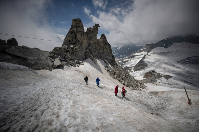 Ice swimmers walk uphill the glacier after they swum in a filled up water kettle in an ice cave inside the Nature Ice Palace, with a hight of 3,250 meters (10,663 feet) above sea level, at Hintertux Glacier near Hintertux, some 480 kilometers (298 miles) western of Vienna, Austria, 29 July 2018. President of the Austrian Ice Swimming Association Josef Koeberl invited members of the Association to spend three days in Hintertux, Tyrol, for ice swim training sessions in a 75 meters long and up to 30 meters deep filled up water kettle at the Nature Ice Palace inside the Hintertux Glacier. The glacier meltwater is at minus 0,2 degrees and the air temperature 25 to 35 meters below the surface between 0 and plus 1 degrees. 400-600 visitors a day attend the dry guided tour through the glacier cave of the Nature Ice Palace, which was discovered by Austrian alpine guide Roman Erler and is owned by Austrian administration of state forests. (Photo by Christian Bruna/EPA/EFE)