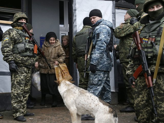Soldiers stand guard as the humanitarian aid is distributed to residents in the town of Debaltseve, Ukraine, Friday, February 6, 2015. (Photo by Petr David Josek/AP Photo)