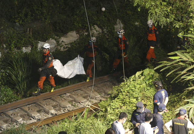 Rescue workers recover a body from a derailed train near the Taroko Gorge area in Hualien, Taiwan on Friday, April 2, 2021. (Photo by Chiang Ying-ying/AP Photo)