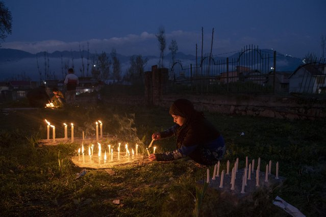 A Kashmiri Shiite Muslim girl lights candles at the grave of her relative to mark Shab-e- Barat, on the outskirts of Srinagar, Indian controlled Kashmir, Monday, March 29, 2021. Muslims visit ancestral graveyards for the salvation of the souls of the departed and also believe that all sins will be forgiven by praying to Allah throughout the Shab-e Barat night. (Photo by Dar Yasin/AP Photo)