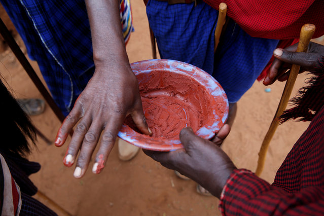 A Maasai holds a bowl of red ochre pigment during an initiation into an age group ceremony near the town of Bisil, Kajiado county, Kenya on August 23, 2018. (Photo by Baz Ratner/Reuters)