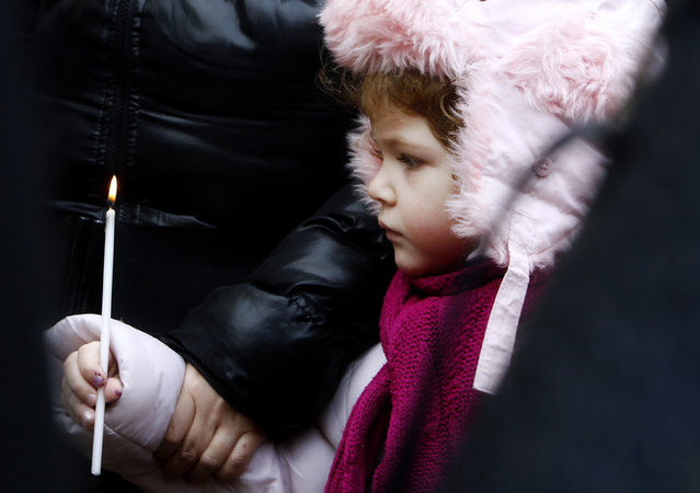 A girl holds at a candle after the holy Christmas liturgy, in front of St. Clement's Cathedral church in Skopje, Macedonia, Thursday, January 7, 2016. Macedonian Christian Orthodox believers celebrate Christmas by the Julian calendar. (Photo by Boris Grdanoski/AP Photo)