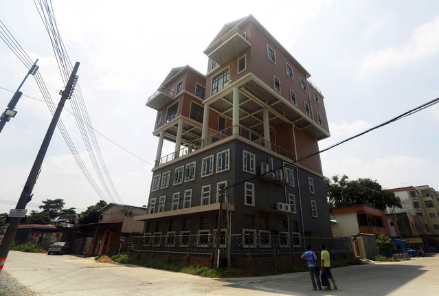 People looks at houses on the rooftop of a factory building in Dongguan, Guangdong province, September 10, 2013. According to local media, the government said the size of the houses was not in line with the original design submitted, thus the construction should be deemed illegal. The houses were completed two years ago. (Photo by Reuters/Stringer)