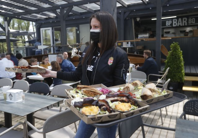 A waitress serves food, in the outside terrace of a bar in Budapest, Hungary, Saturday, April 24, 2021. Hungarians had their first taste of normality in nearly six months Saturday as the outdoor terraces of restaurants and bars filled up in the country's capital, marking the newest round of openings in a country that's been among the hardest hit by the pandemic. (Photo by Laszlo Balogh/AP Photo)