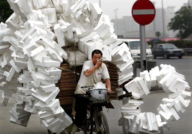 A Chinese man transfers recyclable rubbish which he collects from streets with a three-wheeled flat-bed bicycle in Beijing June 28, 2002. (Photo by Reuters/China Photo)