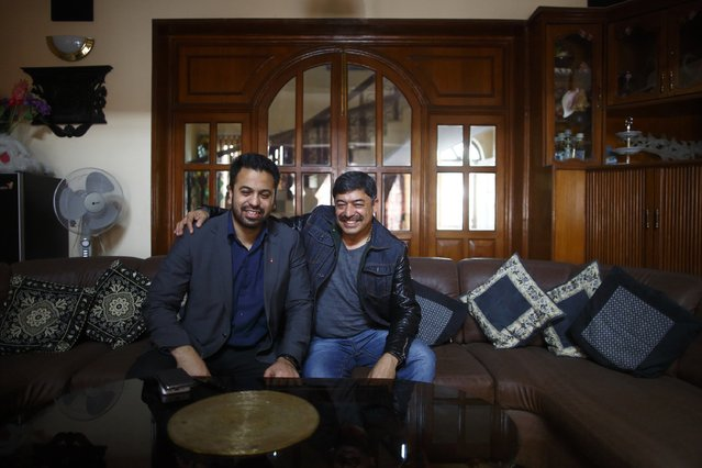 Deepak Malhotra (R), who along with his son Dikesh Malhotra were travelling on a Turkish Airlines plane that overshot the runway at Tribhuvan International Airport, pose for a picture at their home in Kathmandu March 4, 2015. According to local media, all passengers and crew members were rescued. REUTERS/Navesh Chitrakar