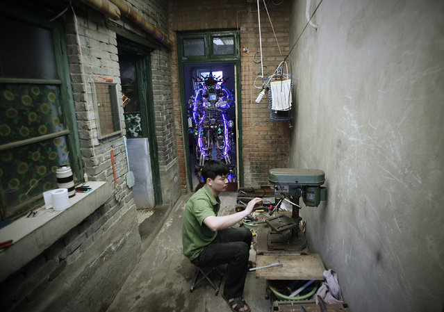 Chinese inventor Tao Xiangli welds a component of his self-made robot (back) at the yard of his house in Beijing, May 15, 2013. Tao, 37, spent about 150,000 yuan (USD 24,407 ) and more than 11 months to build the robot out of recycled scrap metals and electric wires that he bought from a second-hand market. The robot is 2.1-metre-tall and around 480 kilograms (529 lbs) in weight, local media reported. (Photo by Suzie Wong/Reuters)