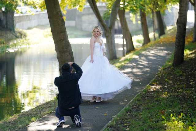Bride Rita Nunes is seen on her wedding day, after having to cancel it previously due to lockdown, posing in autumn sunlight for a wedding photographer amid the coronavirus disease (COVID-19) pandemic in Dublin, Ireland, October 14, 2020. (Photo by Clodagh Kilcoyne/Reuters)