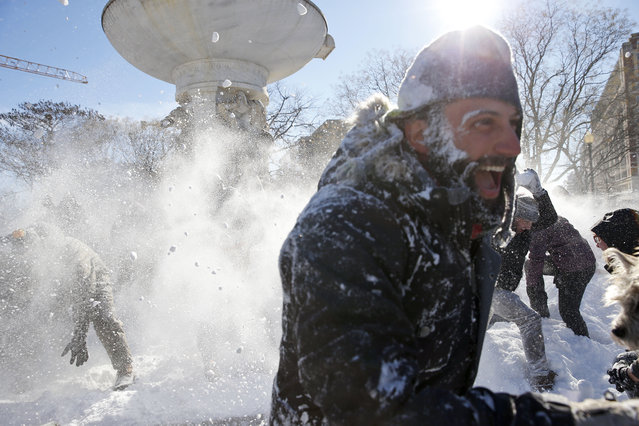 A man runs away covered in snow during an organized snowball fight at Dupont Circle Sunday, January 24, 2016 in Washington. People throw snow during an organized snowball fight at Dupont Circle Sunday, January 24, 2016 in Washington. Millions of Americans were preparing to dig themselves out Sunday after a mammoth blizzard with hurricane-force winds and record-setting snowfall brought much of the East Coast to an icy standstill. (Photo by Alex Brandon/AP Photo)