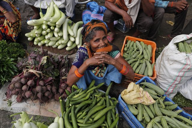 In this June 5, 2021, file photo, a farmer waits for customers at a wholesale market on the outskirts of Prayagraj, in the northern Indian state of Uttar Pradesh, India. On Monday, June 7, 2021, businesses in two of India's largest cities, New Delhi and Mumbai, are reopening as part of a phased easing of lockdown measures in several states now that the number of new coronavirus infections in the country is on a steady decline. (Photo by Rajesh Kumar Singh/AP Photo)