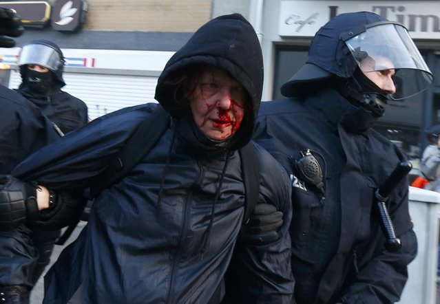 "Policemen detain a wounded anti-capitalist ""Blockupy"" protester near the European Central Bank (ECB) building before the official opening of its new headquarters in Frankfurt March 18, 2015. (Photo by Michael Dalder/Reuters)"