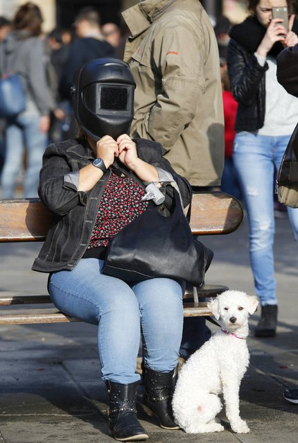 A woman uses a special solar visor as she look at a partial solar eclipse in a square of Pontevedra in the northwest Spain March 20, 2015. (Photo by Miguel Vidal/Reuters)