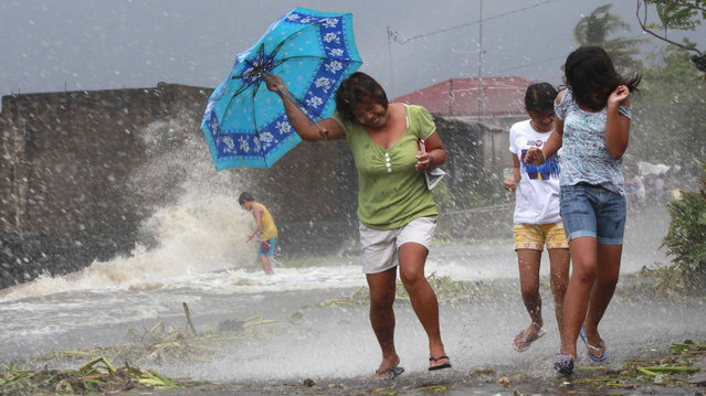 Residents walk along the coastal village while strong winds from Typhoon Haiyan battered Bayog town in Los Banos, Laguna, south of Manila November 8, 2013. Super Typhoon Haiyan, the strongest typhoon in the world this year and possibly the most powerful ever to hit land battered the central Philippines on Friday. (Photo by Charlie Saceda/Reuters)