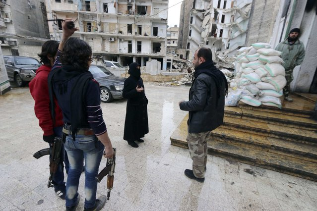 Umm Mohamad (C), a masters graduate and commander of the all-female Mother Aisha battalion, talks with fellow Free Syrian Army fighters in Old Aleppo January 3, 2015. (Photo by Abdalrhman Ismail/Reuters)