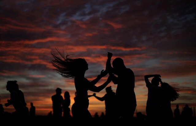 People dance to celebrate Midsummer Eve during sunset at the Amager Strandpark in Copenhagen, Denmark, June 23, 2021. (Photo by Hannah McKay/Reuters)