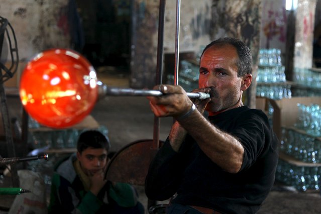 An artisan blows air in a piece of melted glass at a factory that recycles glass in Idlib countryside, Syria November 9, 2015. (Photo by Ammar Abdullah/Reuters)