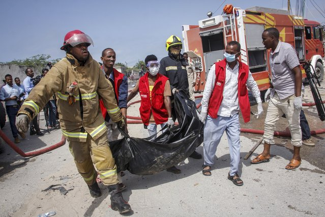 Medical workers carry the body of a civilian who was killed in a suicide car bomb attack that targeted the city's police commissioner in Mogadishu, Somalia Saturday, July 10, 2021. At least nine people are dead and others wounded after the large explosion, a health official at the Medina hospital said, noting that the toll reflected only the dead and wounded brought there. (Photo by Farah Abdi Warsameh/AP Photo)