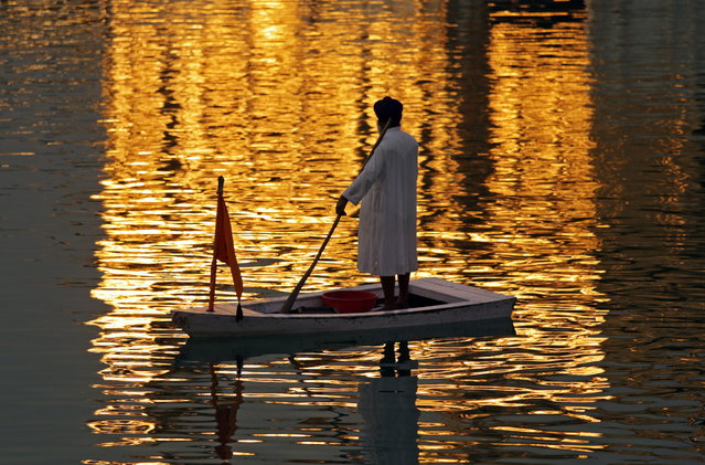 A Sikh man stands on a raft as he performs cleansing work of the Sarowar or the sacred pond of the Golden Temple, the holiest of Sikh shrines, with its golden reflection falling on holy water in Amritsar, India, 23 March 2015. Throughout the year, tourists and pilgrims visit to pay obeisance at the Golden Temple, the most sacred pilgrimage center for the Sikhs all over the world. (Photo by Raminder Pal Singh/EPA)