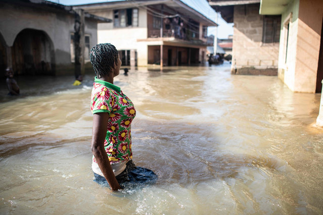 """This handout photo released by the International Federation of Red Cross and Red Crescent Societies (IFRC) on December 20, 2018 shows flood victim Ogatchi standing in front of her home in the flooded main street in her neighbourhood in Anambra West, southern Nigeria, following recent floods that displaced more than 200,000 according to the Red Cross. Nigeria is facing a """"major emergency"""", with tens of thousands of people displaced by recent flooding at risk of hunger and disease if help cannot be got to them, the Nigerian Red Cross said on December 20, 2018. (Photo by Corrie Butler/AFP Photo)"""