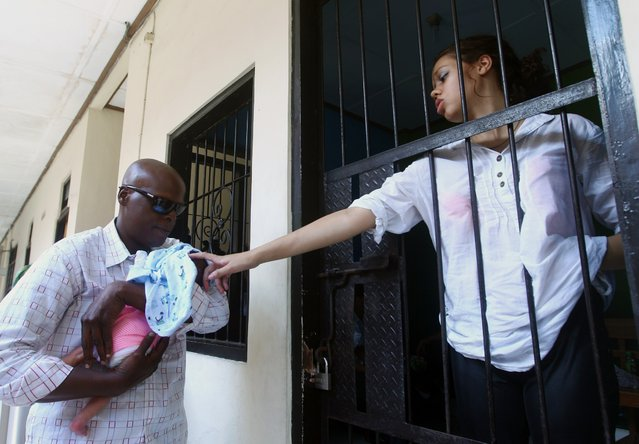 Heather Mack, from Chicago, Ill., right, stands inside a cell as her relative holds her baby before her trial at Denpasar's district court in Bali, Indonesia, Tuesday, March 31, 2015. Tommy Schaefer, 21, and Mack, 19, are being tried separately by Denpasar District Court on a charge of premeditated murder for the death of Sheila von Wiese-Mack at a hotel last August. (Photo by Firdia Lisnawati/AP Photo)